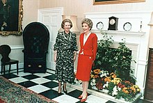 "Thatcher and Nancy Regan stand together in a room containing antique furniture and flowers. A handwritten note at the bottom of the photograph reads ""To Margaret—with respect and affection, Nancy."""