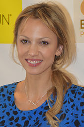 A blonde woman wearing a blue and black shirt smiles towards the camera.
