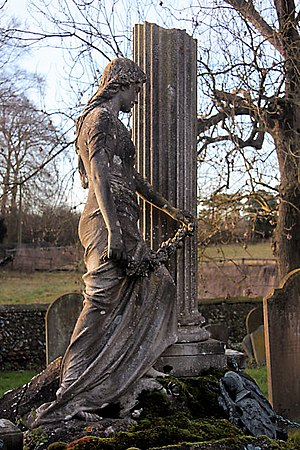"""Herringswell - This memorial, quoted as a """"lush young maiden"""" by Sam Mortlock in his 'Popular Guide to Suffolk Churches', is on the tomb of Herbert Davies, Lord of the Manor of Herringswell, who died in 1899."""