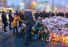 Plusieurs bougies et gerbes de fleurs sous la neige déposées au sol entourées de personnes.