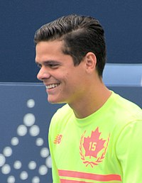 Closeup of Raonic, wearing yellow shirt. He is smiling and looking left.