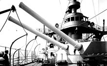 two large rifled cannon pointing out of a turret, aimed over the side of the ship
