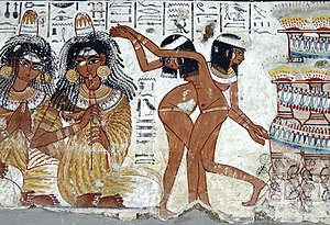 Clothing in the ancient world - Women entertainers perform at a celebration in Ancient Egypt; the dancers are naked and the musician wears a typical pleated garment as well as the cone of perfumed fat on top of her wig that melts slowly to emit its precious odors; both groups wear extensive jewelry, wigs, and cosmetics; neither wear shoes – Tomb of Nebamun c. 1400 BCE