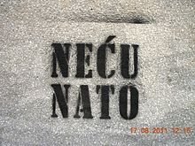 "A white wall with black spray painted words ""Neću Nato"" on it."