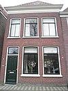 foto van Huis met ingezwenkte halsgevel met siertrossen op de zijden, in fronton gedateerd