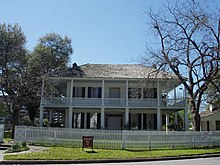 A gambrel-roofed house with large windows, wraparound balcony and first floor porch with Grecian columns. Sashed windows are framed by shutters.