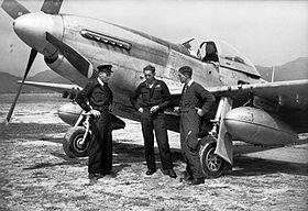 Three men in dark military clothing standing before a P-51 Mustang single-engined fighter plane