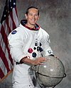 man in space suit, hands on globe, American flag in background