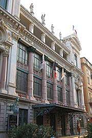 Vue d'un bâtiment de style italien du XVIIIesiècle à colonnes et grandes baies vitrées et statues sur son toit plat.