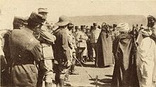 French and Moroccan men crowd around the central figures of Hassan and Poeymirau, standing in discussion