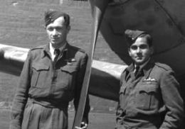 Two men in air force uniforms stand in front of a fighter aircraft