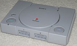 Imatge de la consola PlayStation original en color gris.