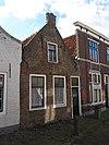 foto van Huis waarvan de van vlechtingen voorziene tuitgevel