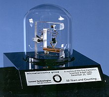 Bell jar covering assembly of plastic and wires, on an engraved plaque commemorating 50 years of the transistor