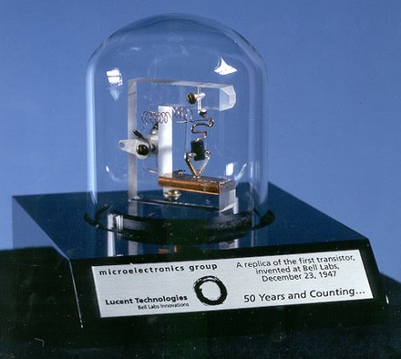 The first transistor, a point-contact germanium device, was invented at Bell Laboratories in 1947. This image shows a replica. Replica-of-first-transistor.jpg
