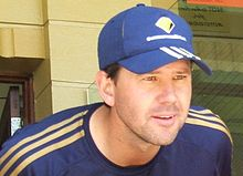 A man stands in front of a brick wall; he is wearing a dark blue cap with matching stripes, and a matching T-shirt. He is cleanshaven bar some stubble and has brown hair.