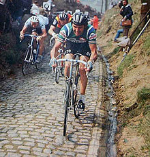 A cyclist riding on a cobbled road