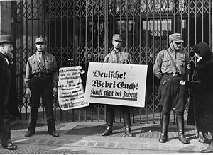 "Anti-Nazi boycott of 1933 - SA paramilitaries in Berlin on April 1, 1933, with boycott signs, blocking the entrance to a Jewish-owned shop. The signs read ""Germans! Defend yourselves! Don't buy from Jews!"""