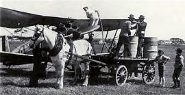 A man refuels a single-engined biplane in a field using barrels on a horse-drawn cart