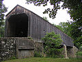 The front entrance and right side of an unpainted covered bridge supported by stone piers