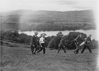 Seven men walking on a golf course