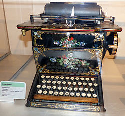 An ornately decorated typewriter with black lacquer, gold detailing and various floral arrangements