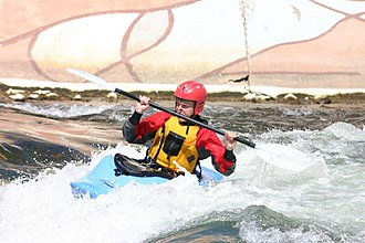 Confluence Outdoor - Playboater on a Wave Sport kayak side-surfing with his paddle in the air