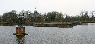 Egmond Abbey - A statue of Lamoraal stands in the middle of the old moat and behind him the Protestant church can be seen that was built on top of the ruins of the old castle Egmond.