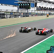 A picture a Lotus E23 Hybrid and a Marussia MR03B driving side by side during the 2015 Brazilian Grand Prix, with sparks flying up from behind the Lotus.