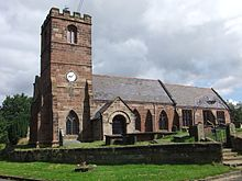 A red sandstone church seen from the south with a battlemented tower on the left