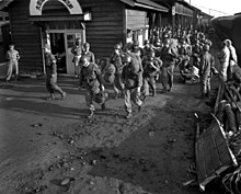 Soldiers carrying their bags off of a train in a Korean train station