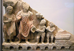 "Scene of KAURWAKII""The Gift of Dirt"", 2nd century Gandhara. The child Jaya, said to be reborn later as Asoka, offers a gift of dirt (which, in his game he imagines as food) to Buddha, hereby acquiring merit, by which the Buddha foresees he will rule India and spread the Buddhist faith."