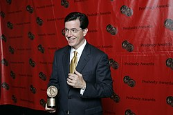 Colbert holding a Peabody Award and giving a thumbs up