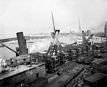 Una fotografia in bianco e nero di vagoni ferroviari di minerale di ferro in un molo di una nave