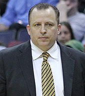 A man with dark hair, wearing a black suit, white shirt and tie, at a basketball game.