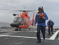 U.S. Coast Guard Seaman Leon Chingcuangco, foreground, assigned to maritime security cutter USCGC Bertholf (WMSL 750), removes tiedowns as part of landing operations in the Bering Sea with a MH-65 Dolphin 120824-G-VS714-018.jpg