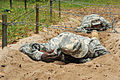 U.S. Soldiers with Headquarters and Headquarters Company, 18th Combat Sustainment Support Battalion low crawl under barbed wire during obstacle course training at the 7th Army Joint Multinational Training 140904-A-BS310-133.jpg