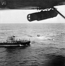 An aerial photograph of a surfaced submarine in choppy sea; a small ship is close by and both appear to be stationary. Part of the aircraft's left wing can be seen, with a bomb hanging from it.