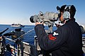 US Navy 030329-N-3235P-510 Operations Specialist 2nd Class Eugene Gant watches a contact on the horizon through the Big Eyeswhile standing the Forward Lookout Watch on the Signal Bridge aboard USS Cape St. George (CG 71.jpg