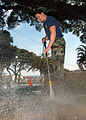 US Navy 050324-N-3019M-002 Engineman 1st Class Joe Sweeting, assigned to Mobile Diving Salvage Unit One (MDSU-1), uses a pressure washer to clean a sidewalk and remove unwanted debris during a community relations project.jpg