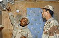 US Navy 051128-N-3750S-254 U.S. Navy Steelworker 2nd Class Jesus Cepeda, left, explains how to control an air conditioner to an Iraqi Security Force (ISF) soldier at an ISF camp.jpg