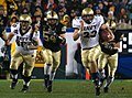 US Navy 051203-N-2383B-223 U.S. Naval Academy Midshipman fullback Adam Ballard (22) rushes for one of two touchdowns while being persued by Army defenders Cason Shrode (54) and Taylor Justice (42).jpg