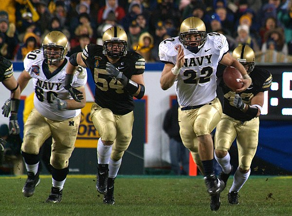 Fullback Adam Ballard (22) rushes while being pursued by defenders Cason Shrode (54) and Taylor Justice (42) during the Army-Navy Game game, a college football rivalry in the United States US Navy 051203-N-2383B-223 U.S. Naval Academy Midshipman fullback Adam Ballard (22) rushes for one of two touchdowns while being persued by Army defenders Cason Shrode (54) and Taylor Justice (42).jpg