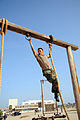 US Navy 080715-N-2959L-349 Seaman Apprentice Eduardo Martinez concentrates on maneuvering to the next rope during and obstacle course.jpg
