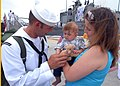 US Navy 090523-N-0486G-012 Boatswains Mate 3rd class Jeremy Allan hands a teddy bear to his 5-month old son as they meet for the first time. Allan returned from a six-month deployment aboard the guided-missile frigate USS Rober.jpg