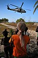 US Navy 100125-N-4774B-414 Haitians citizens watch an SH-60F Sea Hawk helicopter, assigned to the Dragonslayers of Helicopter Anti-submarine Squadron (HSC) 11, deliver fresh water from the guided-missile cruiser USS Bunker Hill.jpg
