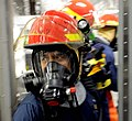 US Navy 100327-N-7653W-154 Chief Operation Specialist Anthony Morales help Sailors contain a fire during a damage control training drill.jpg