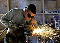 US Navy 100422-N-6357K-008 teelworker Constructionman Justin Sneed perates a gas cutter to modify a support post to be used in fabricating a maintenance catwalk at a water treatment facility at Naval Station Rota, Spain.jpg