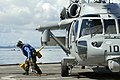 US Navy 101003-N-8335D-199 Seaman Michael Tarquino runs for safety after removing a chock and chain from the wheel of an MH-60S Sea Hawk helicopter.jpg