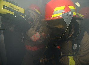 USS Bataan (LHD-5) - Gulf of Oman, (December 15, 2011). A firefighting team enters a smoke-filled room to extinguish a mock fire during a general quarters drill aboard Bataan